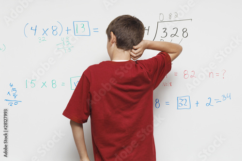 Schoolboy standing against whiteboard, back view