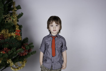 Child posing near a Christmas tree