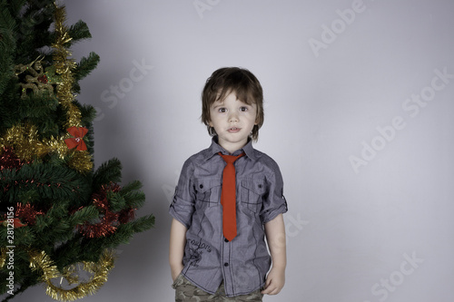 Child posing near a Christmas tree