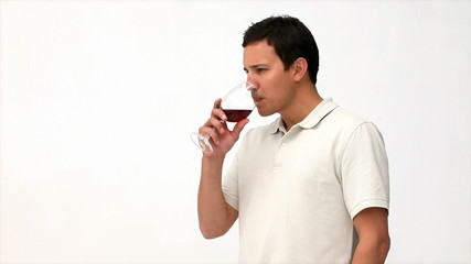 Happy man tasting red wine against a wine background