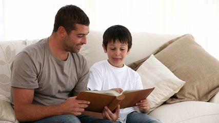 Father and son looking at a book on the sofa