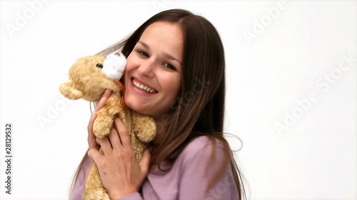Young woman playing with a teddy bear against a white background