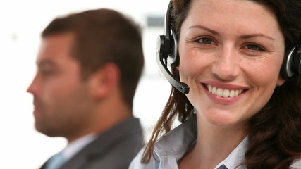 Happy representative with colleague working in a call center