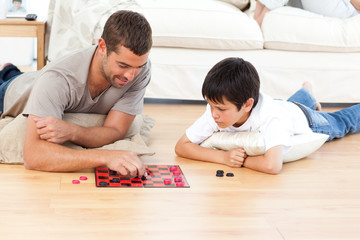 Handsome man playing checkers with his son lying on the floor