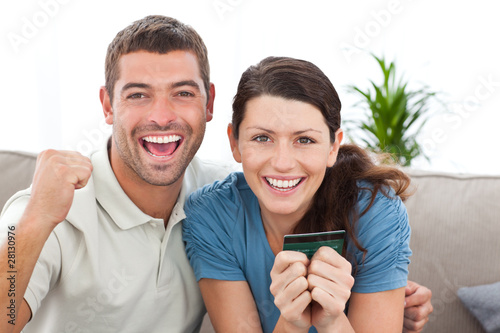 Portrait of a happy couple holding their credit card on the sofa