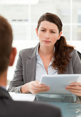 Serious businesswoman questionning a man during a meeting