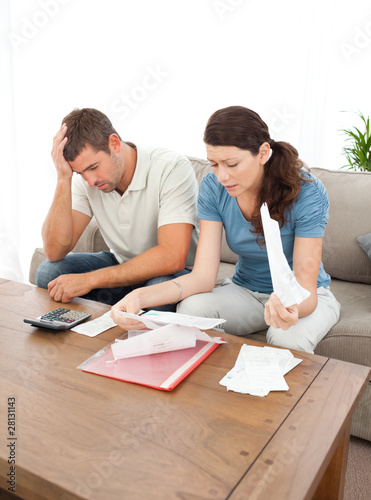 Worried couple looking at their bills in the living room