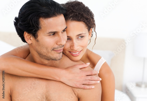 Lovely couple hugging sitting together on their bed