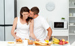 Affectionate man kissing his girlfriend while cutting bread