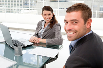 Happy businesspeople working together on a laptop