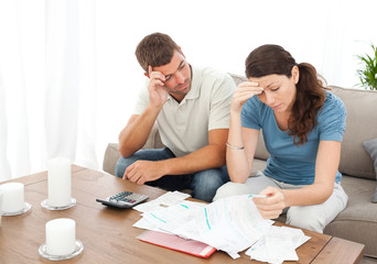 Worried couple doing their accounts in the living room
