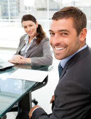 Cheerful business people sitting at a table with a laptop