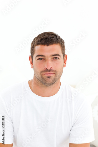 Portrait of a serious man sitting on his bed