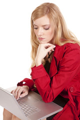 woman red coat thinking computer