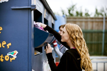 Two teenage girls recycling clothes