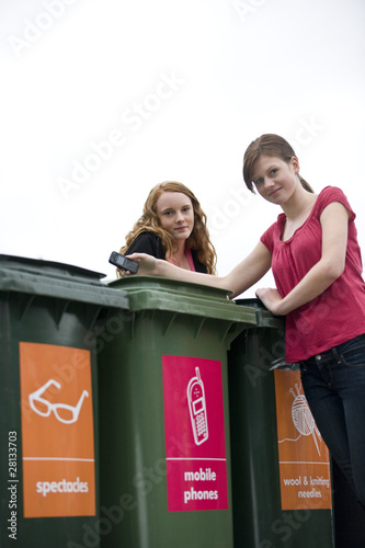 Two teenage girls recycling a mobile phone