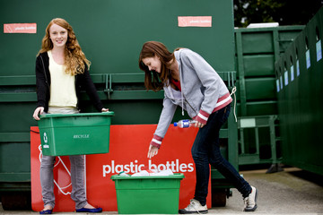 Two teenage girls recycling plastic bottles