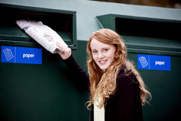 A teenage girl recycling newspapers