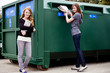 Two teenage girls recycling newspapers and magazines