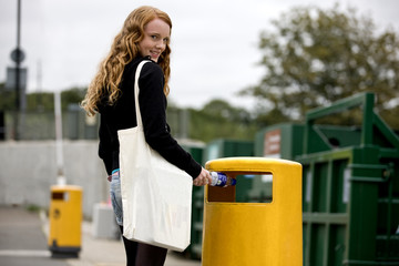 A teenage girl putting a plastic bottle into a rubbish bin