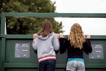 Two teenage girls looking into a recycling container