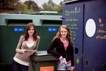 Two teenage girls recycling cds
