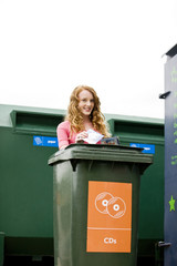 A teenage girl recycling cds