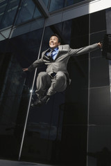Businessman holding briefcase Jumping outside building, low angle view