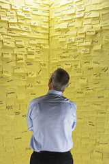 Middle-aged man standing in front of wall covered in sticky notes, back view