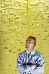 Middle-aged man in glasses, standing in front of wall covered in sticky notes