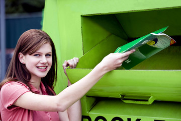 A teenage girl recycling a school textbook