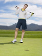Young golfer standing on green, portrait