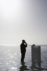 Silhouette of business man using phone on filing cabinet in sea, side view, elevated view