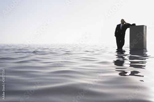 Business man leaning on filing cabinet standing in sea