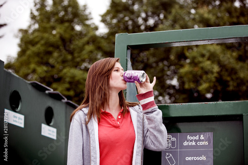 A teenage girl drinking a soft drink in a recycling centre