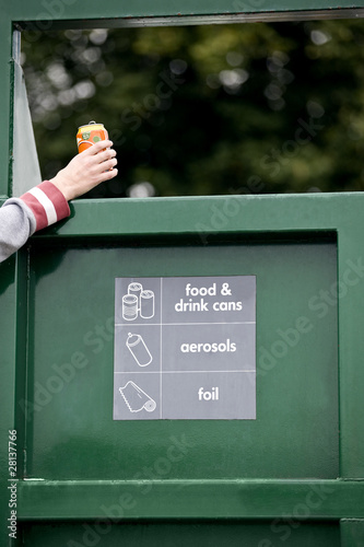 A teenage girl recycling a drink can