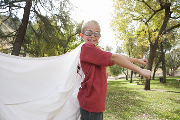 Boy 7-9 wearing cape and swimming goggles