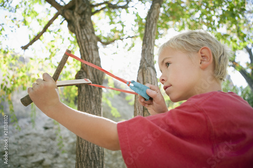 Boy 7-9 using slingshot
