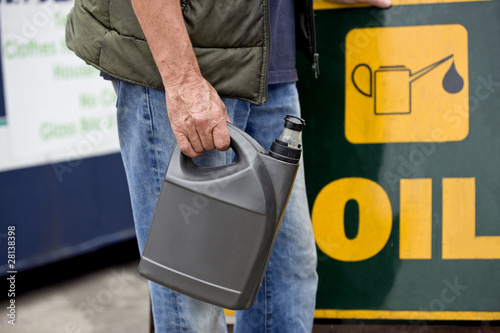 A senior man holding an oil container in a recycling centre