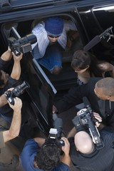 Male celebrity and paparazzi, high angle
