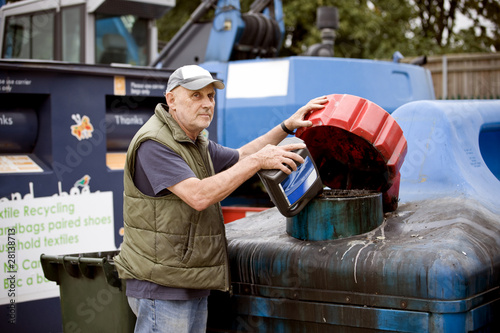 A senior man pouring oil into a recycling container