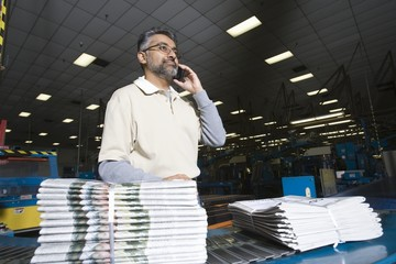 Man using telephone in factory, with newspapers