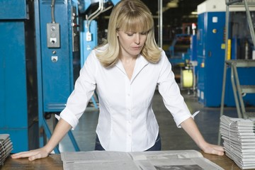 Woman checking newspaper in factory
