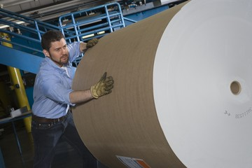 Man pushing huge roll of paper in newspaper factory