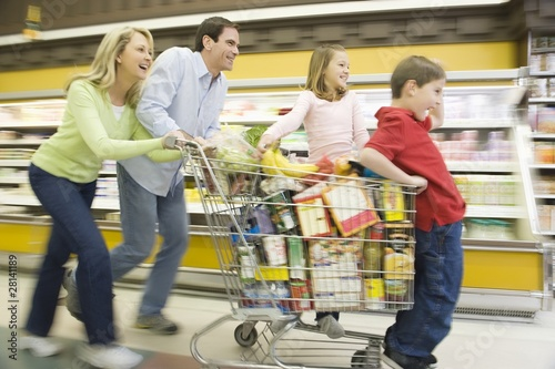 Family of four run with full shopping trolley
