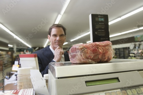 Mature man looks at selected meat on weighing machine