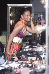 Woman applies makeup in dressing room mirror