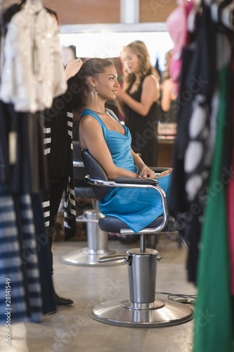 Woman in blue dress sits having hair styles