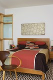 Patchwork quilt on bed in Autumn colours
