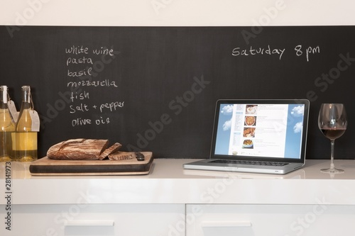 Chalkboard list with cut bread and laptop computer